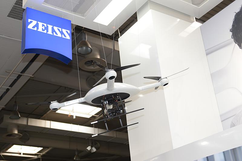 Carl Zeissブースに展示された独Microdronesのクアッドリコプター「md-4-1000」。過去にPhotokinaでもデモされていたが、ミラーレス級のカメラを搭載して飛行可能。スポーツカムなどを使って一人称視点の映像を「cinemizer OLED」に表示できる