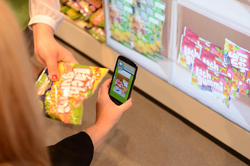 ARを使った買い物ソリューションのデモ。商品が表示されているディスプレイにスマートフォンのカメラをかざすと、商品を認識してカートに品物が追加される