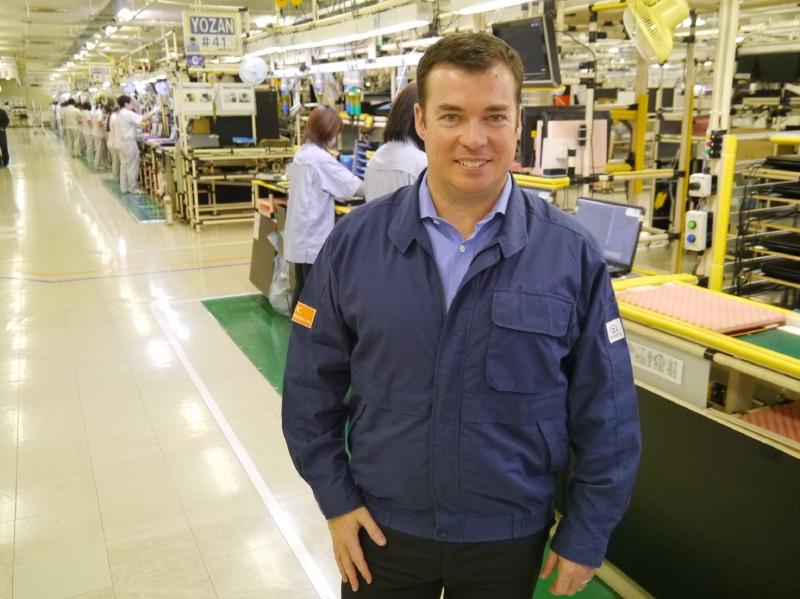 米沢事業場の生産ラインの前に立つNECパーソナルコンピュータのロードリック・ラピン社長