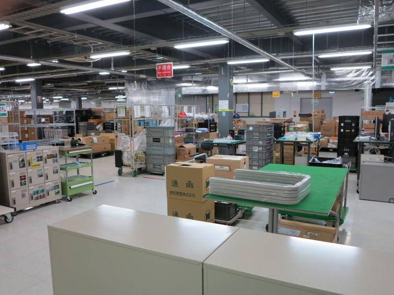 受入検査場。奥に荷受場がある。部品が到着すると抜き取り検査を行なって倉庫へと移動させる。荷受が工場の端ではなく中央で行なわれているのが特徴