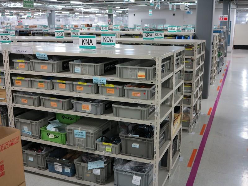 倉庫はフリーロケーションで、部品の空きが出ると後から入ってきた部品がそこに置かれることで、スペースを効率的に利用できる仕組み。棚上部の3ケタのアルファベットはロケーションを表しており、どの部品がどのロケーションに置かれているかはシステムで管理されている
