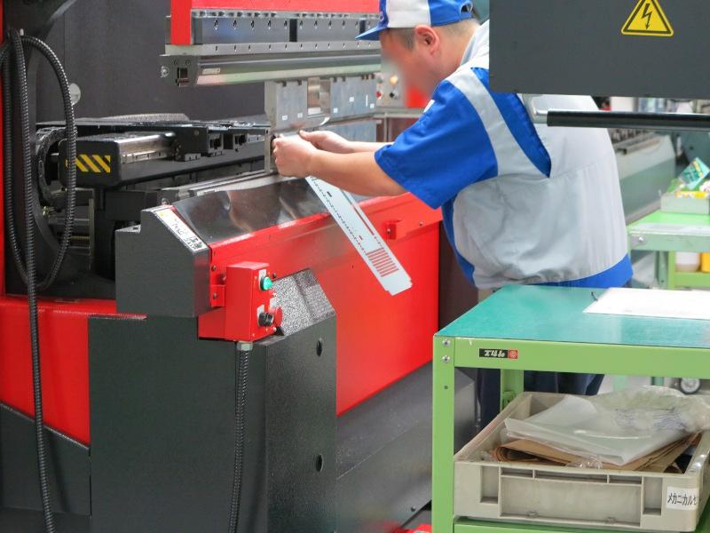 プレスブレーキを用いて鉄板を曲げる工程。鉄板の向きを揃えて順番通りにセットする工程をスタッフ(人)が、寸法に沿って曲げる工程をプレスブレーキ(機械)が受け持つ。少量多品種ということで全自動ではないのが特徴