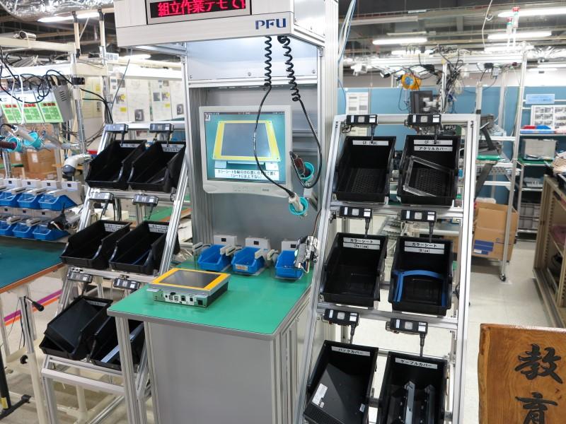 同社が採用している「組立アシストシステム」の工場見学者向けデモコーナー。組立に使用する順に電動ドライバーなど工具の置き場所が点灯する。また電動ドライバは持っただけでは動作せず、ネジを箱から取り出すことでセンサが感知し、はじめて動作する仕組み