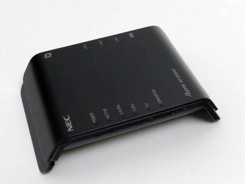 本体。横置き(壁掛け)状態正面やや左上から。ロゴや動作ランプは天面側にある。ランプの機能を示す記号の刻印が正面側にある