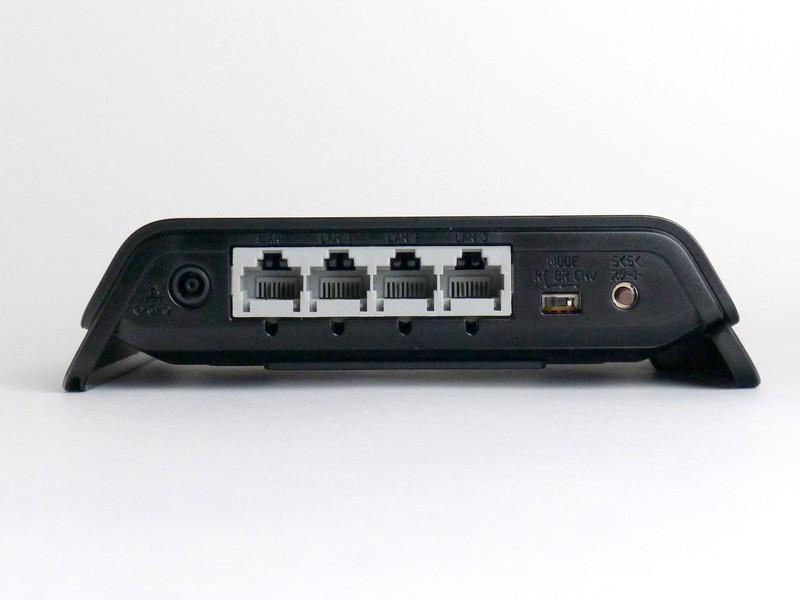 横置き状態背面。左から電源コネクタ、WAN×1、LAN×3、動作モード切り替えスイッチ、「らくらくスタート」ボタンが並ぶ