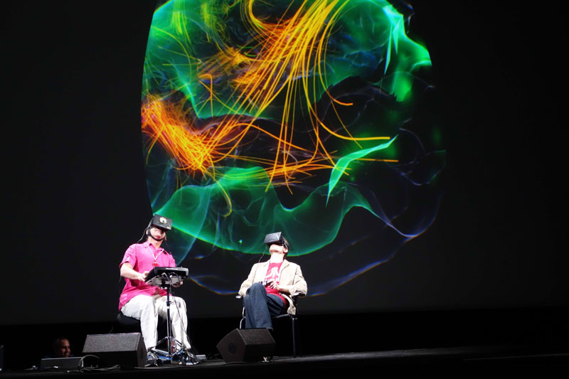 並んで座るゲームプレーヤーと観察者、背後はプレーヤーの脳内のリアルタイム映像
