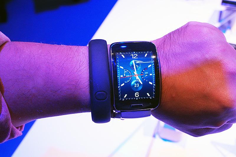 腕に付けてみた様子。左側はサイズ比較用に私物のNike Fuelbandを巻いた。男性としてはやや手首は細いほうだが、それでもこれだけの大きさがあり、腕時計というよりは腕輪