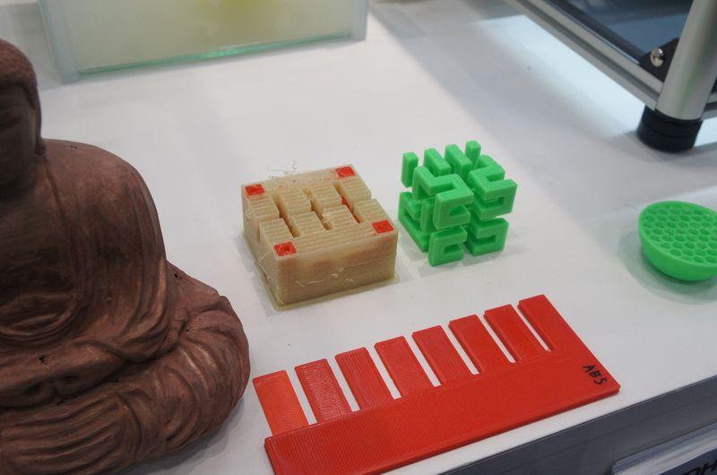 MF-2000の出力例。左側のベージュ色部分はサポート材として利用されるPVAであり、水につけることで、溶けて赤色のPLAだけが残る。右側の緑色の物体は、サポート部分を溶かした後のもの