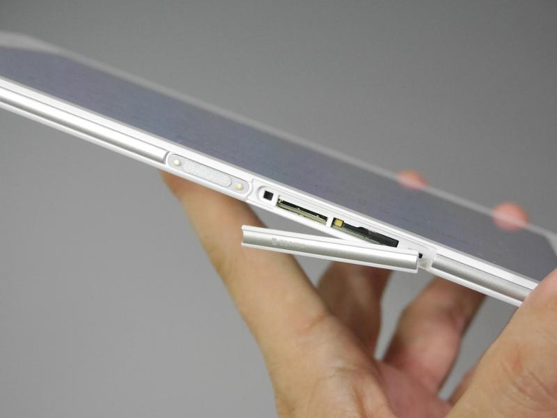 左側面にはmicroSDカードスロットと、SIMカードスロットを備える。左隣に見えるのは充電クレードルに立てる際の端子