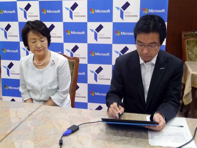 2010年6月、日本マイクロソフトと横浜市、横浜市教育委員会は、世界で幅広く活躍する人材の育成や、ICTの活用による先進的な教育環境づくりに、連携して取り組むことで合意した。横浜市長の林文子氏は、ダイエー時代に会長兼CEOとして、樋口氏とともに、ダイエー再建に取り組んだ仲でもある。樋口氏は、「前職でご一緒させていただいた林市長と一緒に働くことができることを、喜んでいる」とコメント。林市長も、「かつて仕事を一緒にした経験が、今回の協業に繋がった」と話した。また、2013年7月には、「ICTの活用による女性の多様な働き方支援」や「オープンデータの推進による市内経済の活性化」で新たな連携を発表。この時は、Surfaceを使ったデジタルデバイスで、締結の覚書に署名を行なった。左は樋口氏の署名を見守る林市長