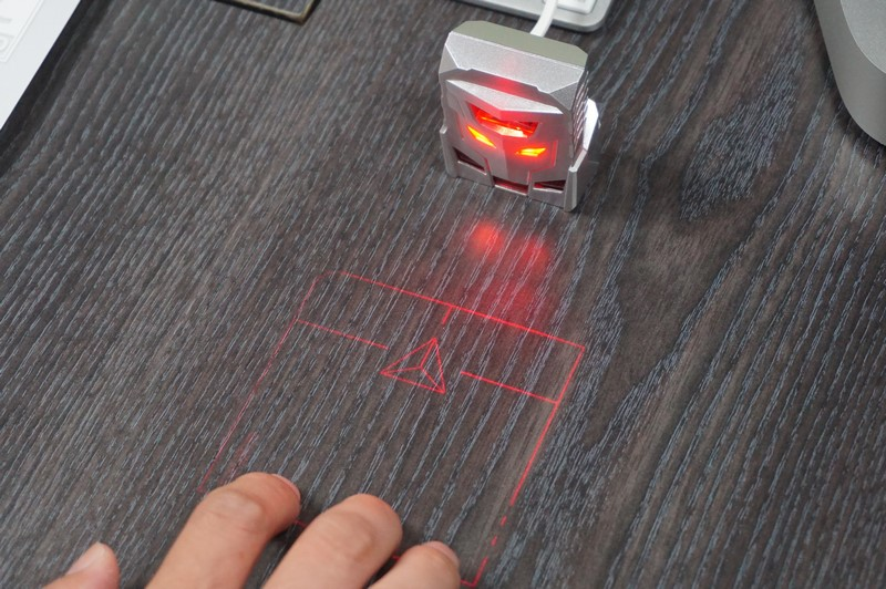 SerafimのODiN。机の上に描画されている線の内側で指を動かすと、その動きを検知してポインティングデバイスとして利用できる。中央の三角形がプログラマブルなボタン、PCとはUSBケーブルで接続する