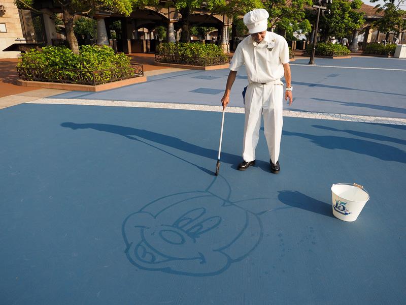 カストーディアルキャストが、トイブルーム(ほうき)を筆のように操り、水を使ってさまざまなアートを地面に描く