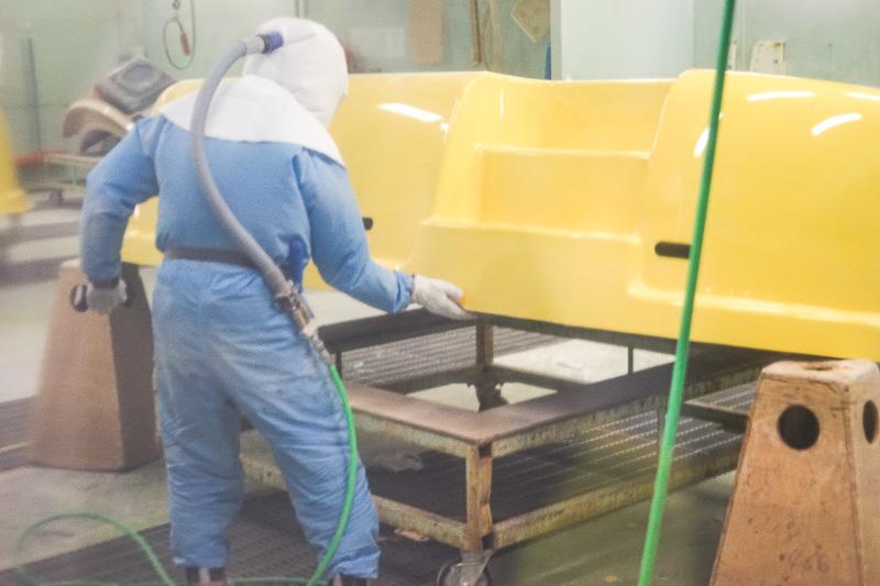 フチをトリミングする作業。頭部を覆うマスクに空気を入れ、全身を防護しての作業