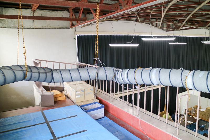 講堂内吹き抜けの2階まで引き込み、送風管に穴を開けて冷風を送り出している