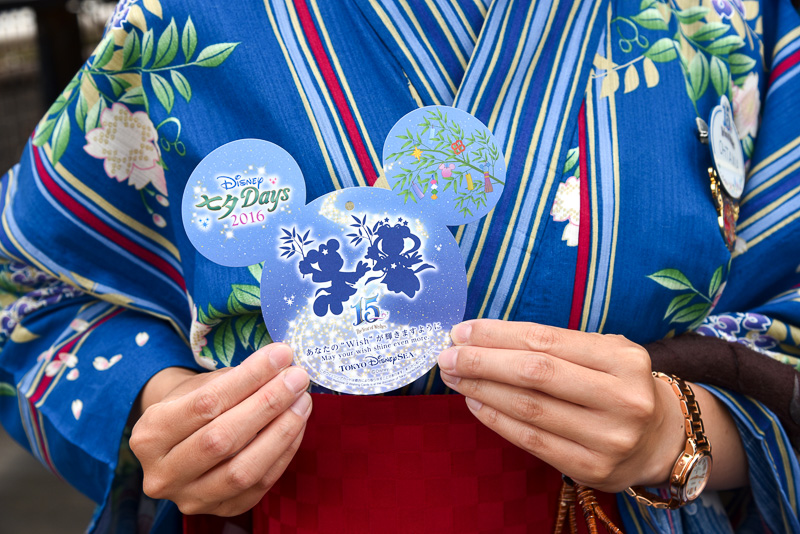 ピア32の入り口付近でキャストがウィッシングカードを配布中。よく見るとカードにも隠れミッキーらしきシルエットが! 東京ディズニーシー15周年のロゴ入りのスペシャルな1枚となっている。なお、カードの配布は開園から22時まで。もちろんキャストの浴衣には隠れミッキーらしき形も