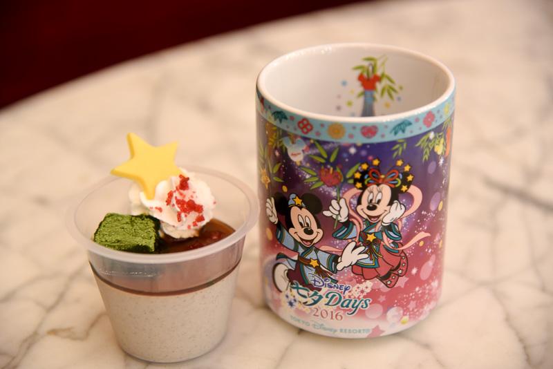 パークでも人気の和スイーツは、東京ディズニーシー、東京ディズニーランドの両パーク共通のメニュー。スーベニアカップには、天の川をバックに七夕コスチュームのミッキーマウス、ミニーマウス、そしてデイジーダックとドナルドダックのイラストが描かれている。スーベニアカップは湯のみ型のため、自宅でもお茶を淹れて使える。「黒ゴマムース、スーベニアカップ付き」(720円)