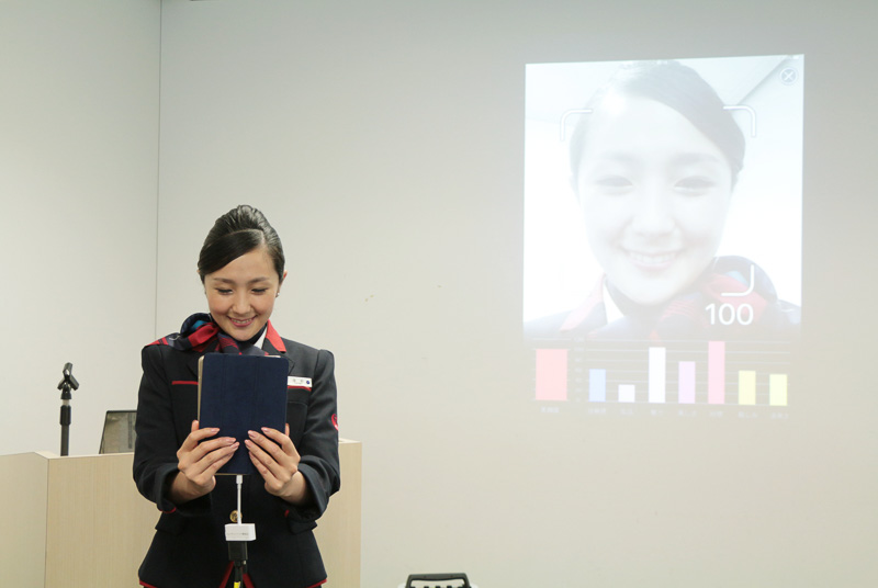 自分の顔をディスプレイで確認しながら100%の笑顔をする横野氏
