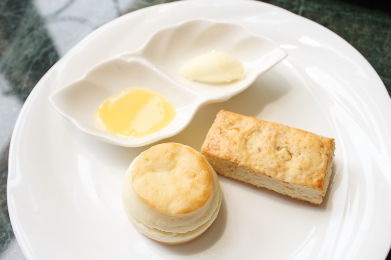 写真左が「プレーン」、右が「ココナッツ&オレンジ」のスコーン。クロテッドクリームとレモンクリームが添えられている