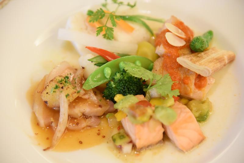 中央奥が「白身魚のナージュ カルダモン風味」、以下時計回りに「ローストチキン ロメスコソース」「サーモンのサルサソース」「ポークのハニーマスタードソース」、中央が「温野菜」
