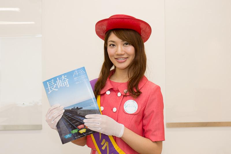 大村市フラワー大使・花菖蒲の鐘江美沙紀さんが手にしているのは「長崎デスティネーションキャンペーンガイドブック」のダイジェスト版。全48ページの完全版はJRグループ6社が全国約1000の主要駅で配布する予定だ
