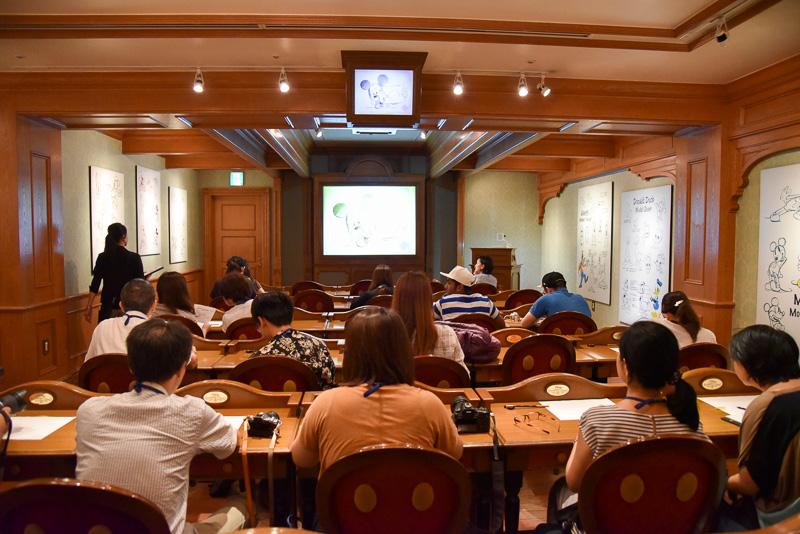 受講する会場の様子。机と椅子がズラリと並ぶ。前方には大型のスクリーンを設置