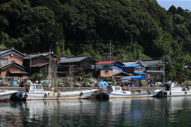 間口の狭い切妻屋根が規則正しく並ぶ沖島漁港の風景