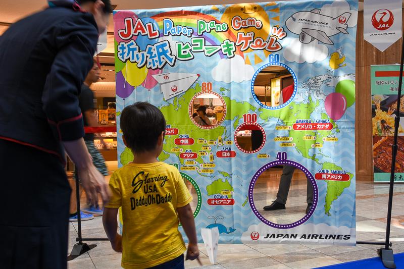 """作った折り紙ヒコーキは、世界地図が描かれた""""的""""に向かって投げ、得点が書かれた穴に入れば景品をもらえる"""
