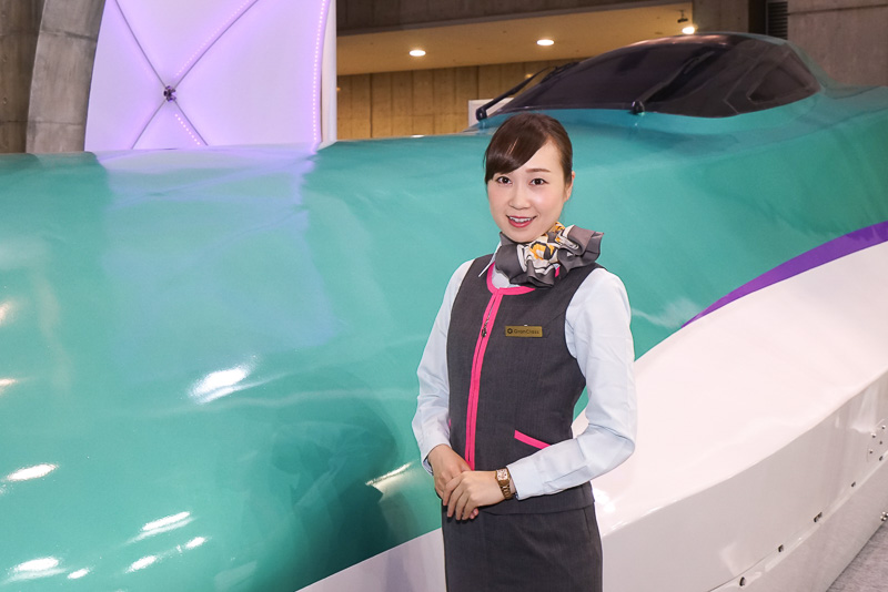 実物大の北海道新幹線模型と北海道新幹線グランクラス車内で手伝いをするグランクラス専任アテンダント