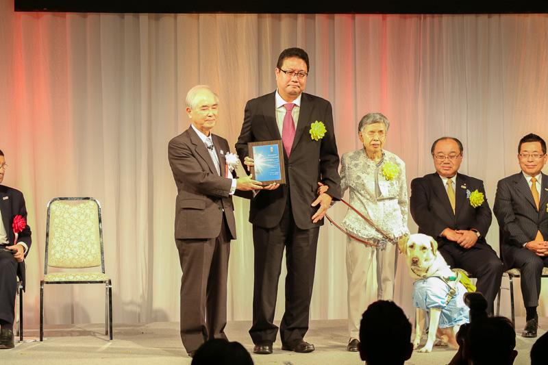 写真左から山口氏、クラブツーリズム株式会社 代表取締役社長 小山佳延氏、発案者の望月操氏と盲導犬のエース
