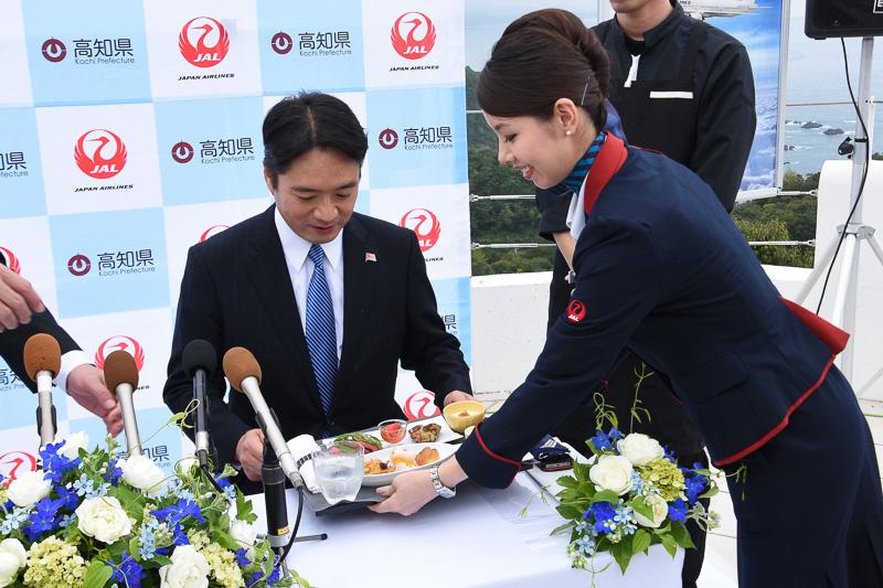 高知県出身の宮地CA(客室乗務員)が尾﨑知事に下旬提供の機内食をサービス