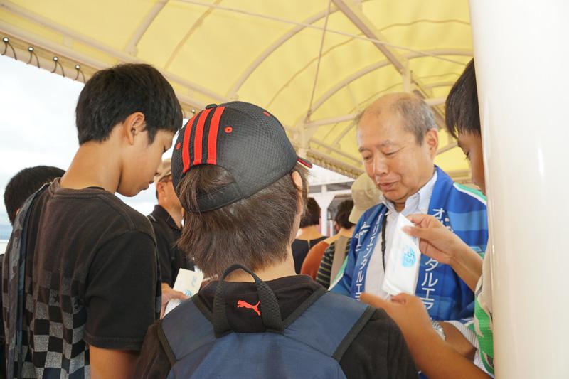 ポップコーンを無料配布する列で、小澤社長自らノベルティグッズの配布などを行なった