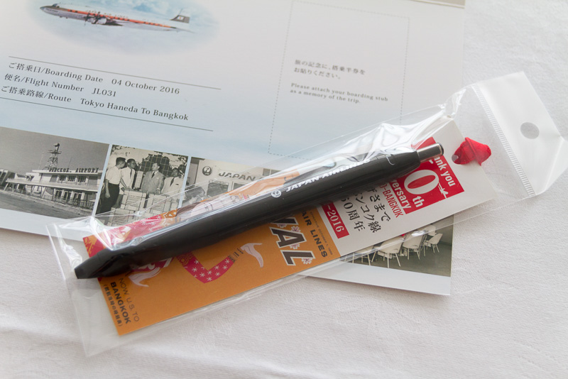 乗客に配布された観光パンフレット、旅の指さし会話帳、搭乗記念カード、JAL特製ボールペン