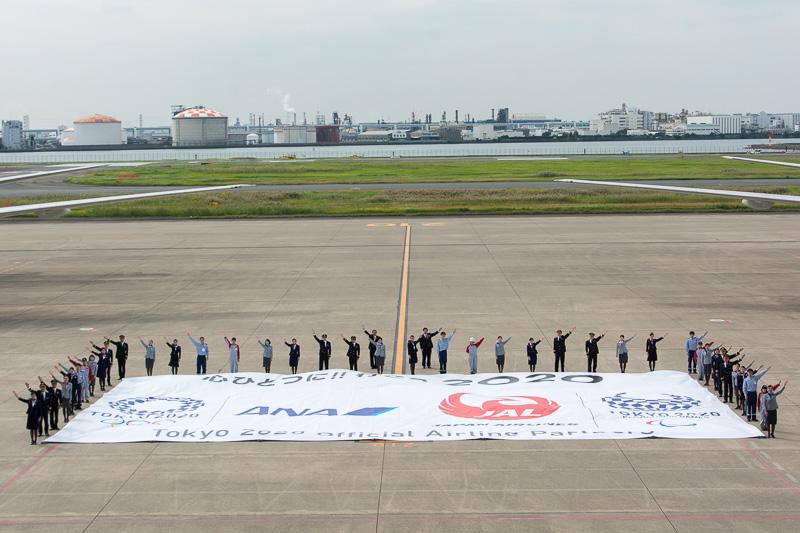 2機の間に敷かれた共通ロゴ。周囲はANAとJALのスタッフが交互に並んでいる。写真右の奥はANAの篠辺社長とJALの植木社長、手前は左からJALのパイロット、ANAのCA、JALのCA、ANAの整備士が並んでいる