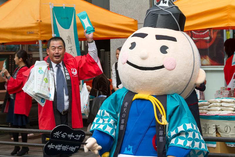 JALの取締役会長である大西賢氏も道行く人に青森をPR。右にいるのは青森県産品をPRするマスコットキャラクター「決め手くん」