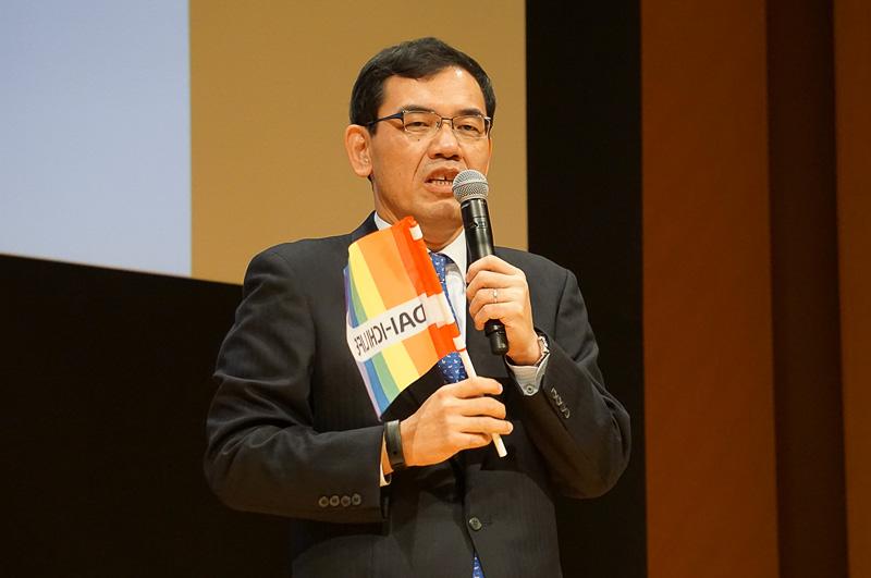 レインボーカラーの旗を持って挨拶をする第一生命保険株式会社 取締役常務執行役員の武富正夫氏