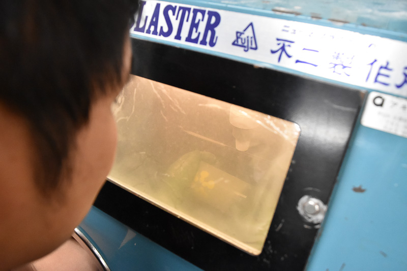 スタッフの方が高圧コンプレッサーを使ってグラスに砂を吹き付けます