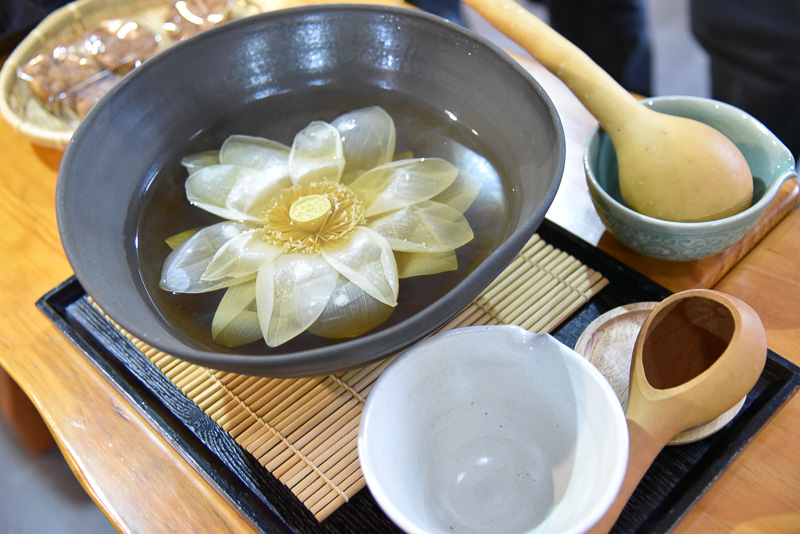 大きな茶器に注がれたハスの葉茶に浮かぶハスの花