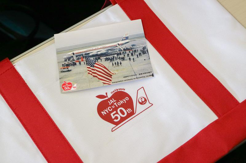 記念品はJALのロゴマークと、リンゴ(the big apple:ニューヨーク市のニックネーム)に「JAL NYC=Tokyo 50th」と書かれたトートバッグ。トートバッグのポケットには1966年(昭和41年)11月12日就航当時の写真と、50周年の感謝のメッセージが印刷されたカードが入っていた