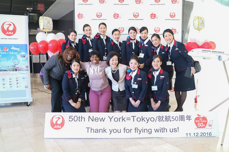 大川順子氏やJL005便に搭乗するCA、空港スタッフらが記念撮影