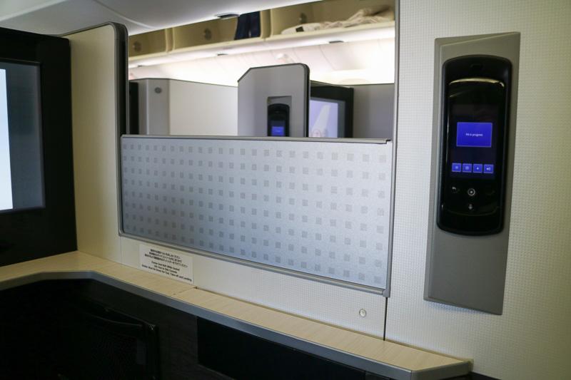 各座席間はプライバシーパーテーションで仕切られており、その開閉もこのボタンで操作する。離着陸時は開けた(下げた)状態、シートベルトサインが消えたあとは基本的には閉めて(上げて)おく