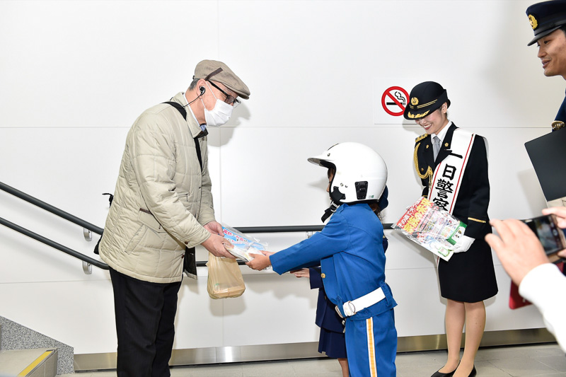 「よろしくお願いしま~す!」とチラシを手渡す園児たちと佐藤署長