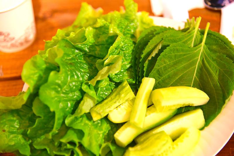 たっぷりの野菜に程よく焼けた肉とコチュジャン、生ニンニクなどをのせて食べる