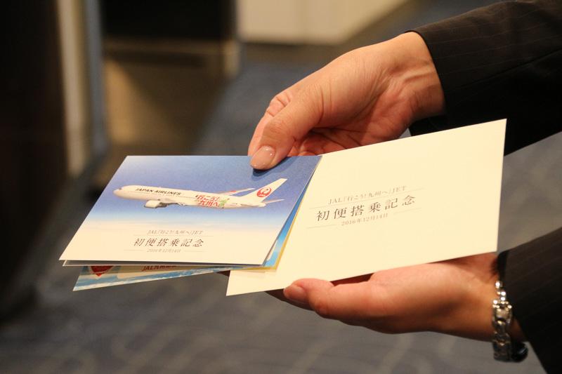 配布された「初便搭乗記念」のカードとステッカー