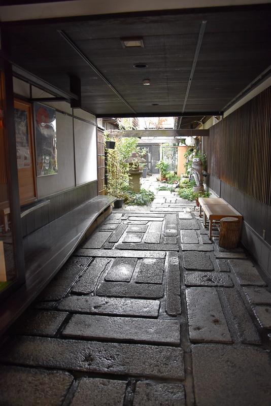 通りに面した暖簾をくぐると小道が現われ、その先にお店の入り口が見えてくる