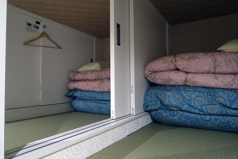 布団は西川産業製。なお写真は男女混合ドミトリーは、間仕切りが扉で開けられるようになっている。複数人で泊まる際に便利だ