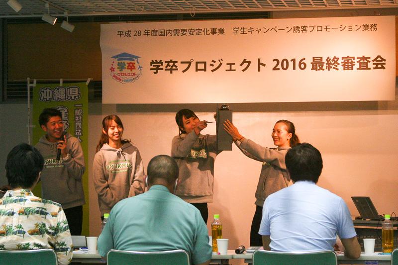 琉球大学の宜野座村プラン。実際に自分たちが楽しんでいる写真で資料を作成。1年後に自分に届くポストカード、手作りのポストなど工夫を凝らしていた。キメのポーズを交えてのプレゼンで、楽しさが伝わってきた