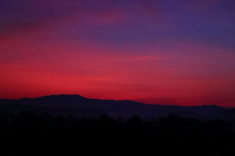 まだ薄暗い時間に出発するときは車窓から日の出が楽しめた。見ているのはラオス側の空だ