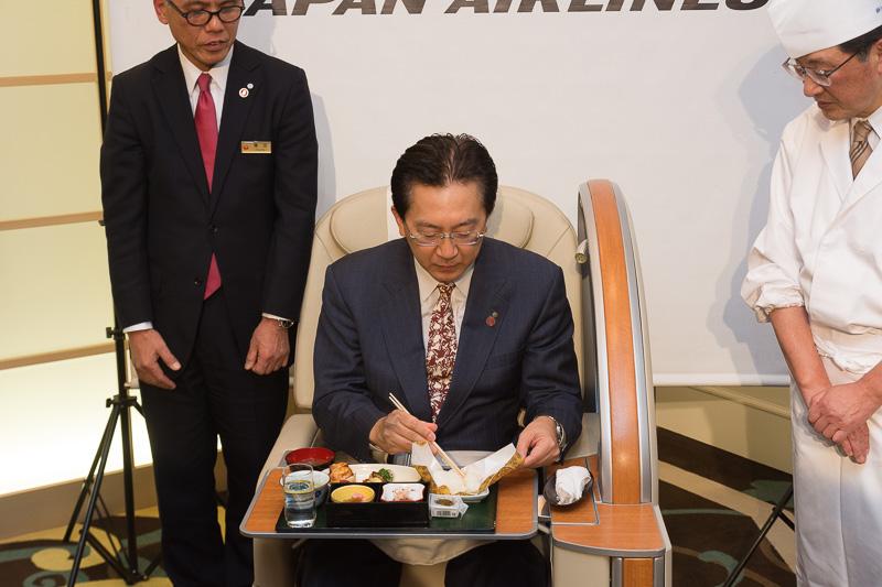 国内線ファーストクラスシートに座って2月上旬提供メニューを試食する岩手県知事の達増氏