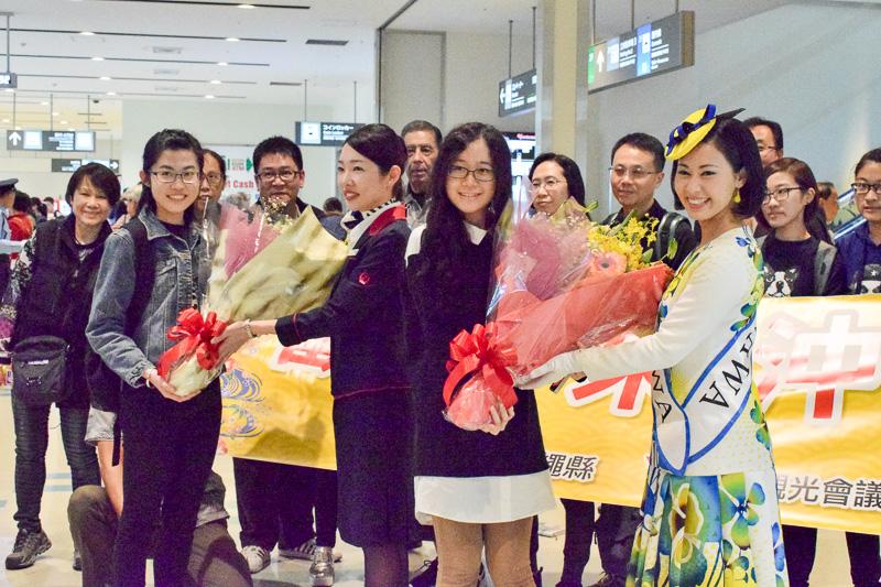 お客様代表として、ティファニー(左)さんとリタさん(右)が、ミス沖縄、JTA客室乗務員より花束を受け取った