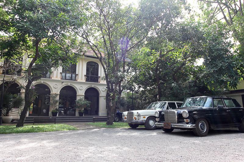 コロニアル様式の建物とクラシックカーが並ぶエントランス